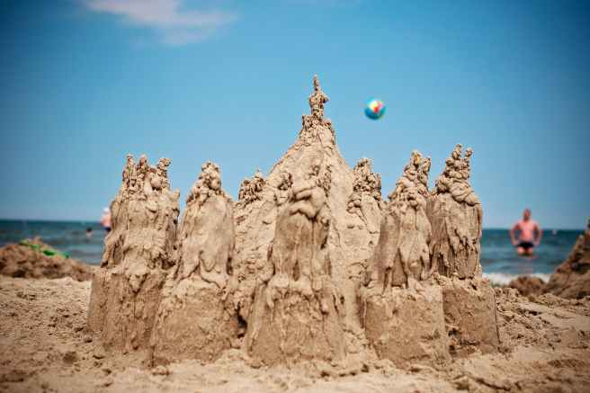 sand sculpture on beach under blue sky